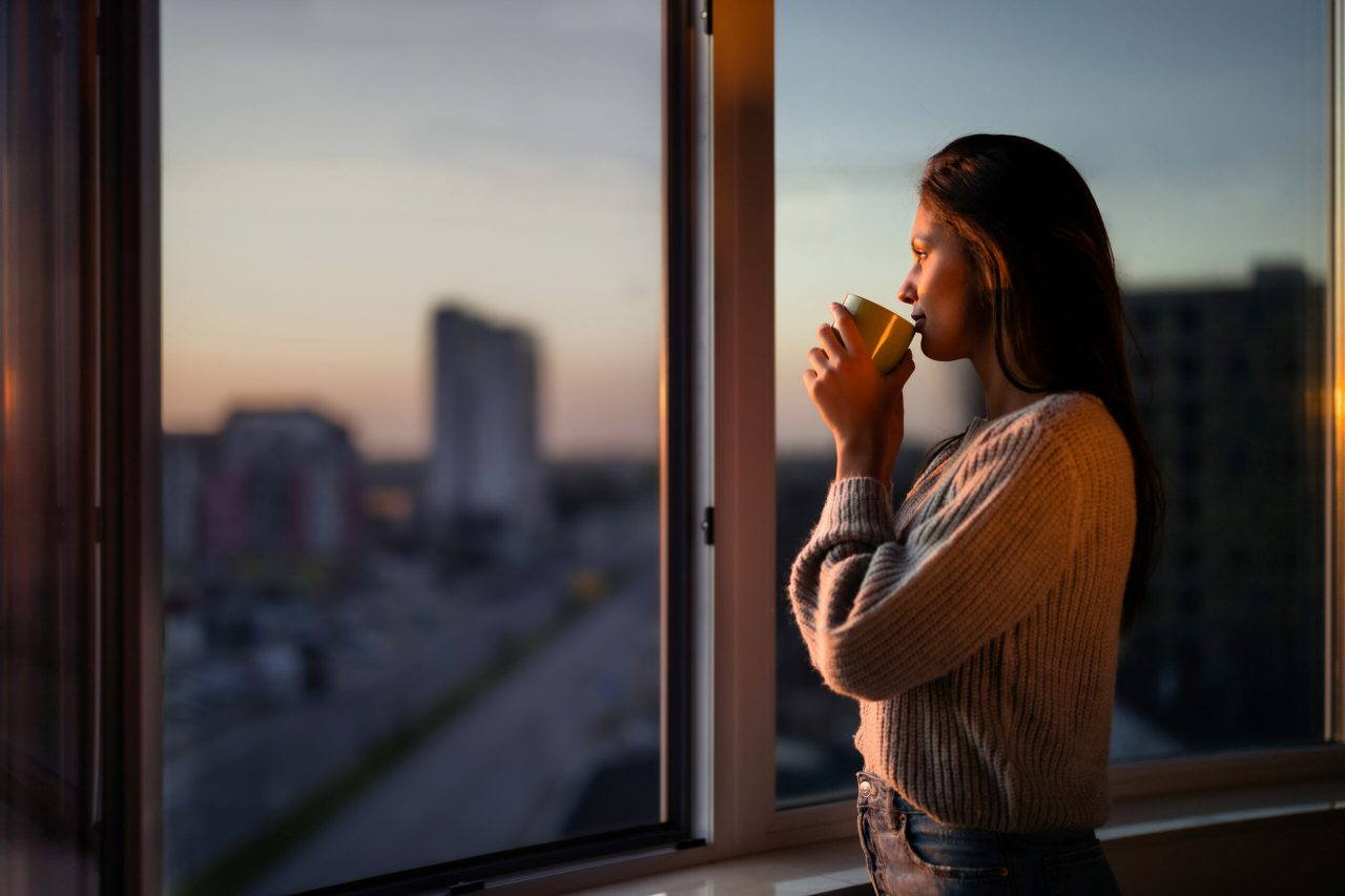 Young woman drinking coffee and day dreaming while looking through window. Copy space.